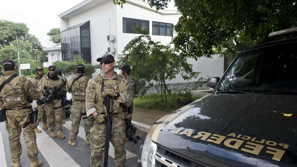 Federal police officers are deployed at the Lula Institute headquarters in Sao Paulo, Brazil on March 04, 2016. Police searched the home of Brazil's powerful ex-president Luiz Inacio Lula da Silva and detained him for questioning Friday in a probe into a huge corruption scheme. Agents searched his house in Sao Paulo, the offices of the Lula Institute, and houses of family members, Jose Chrispiniano, a spokesman for Lula and his institute, told AFP.AFP PHOTO / NELSON ALMEIDA